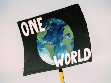A protest sign with a picture of the Earth and the slogan 'One World'