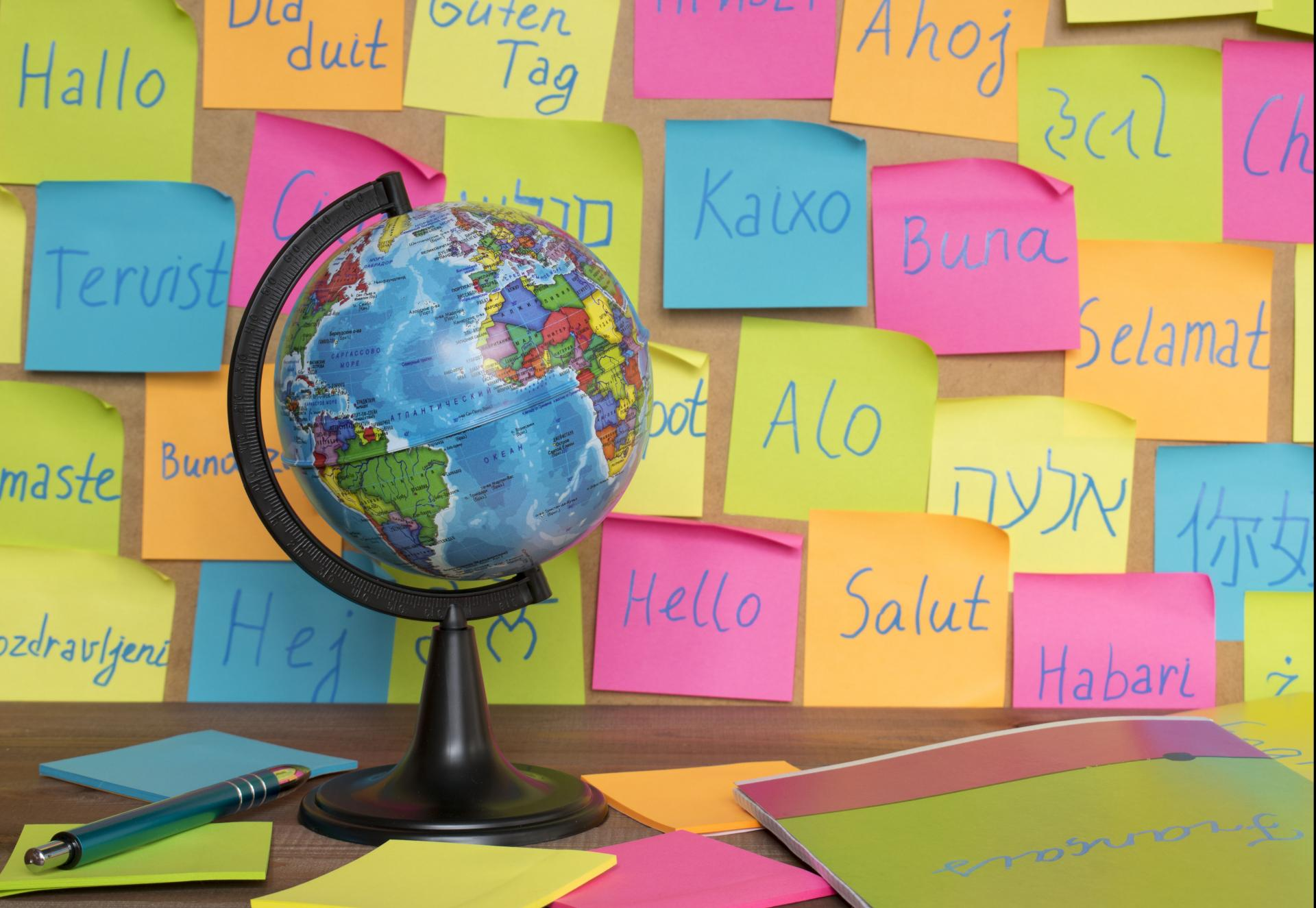 A globe in front of post it notes saying hello in many different languages